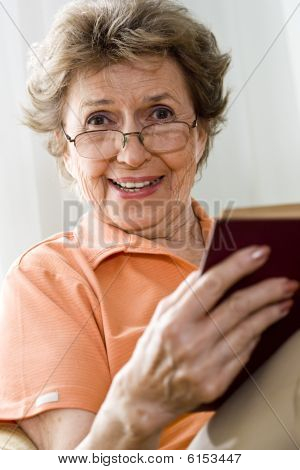 Elderly woman relaxing at home reading a book