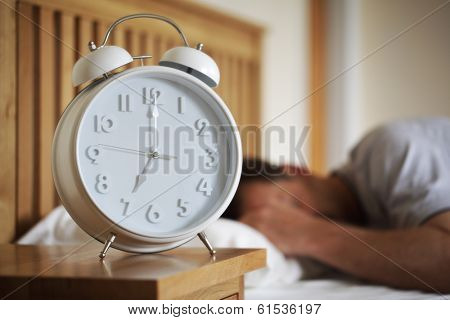 Man sleeping with alarm clock foreground concept for morning, time to wake up or fatigue
