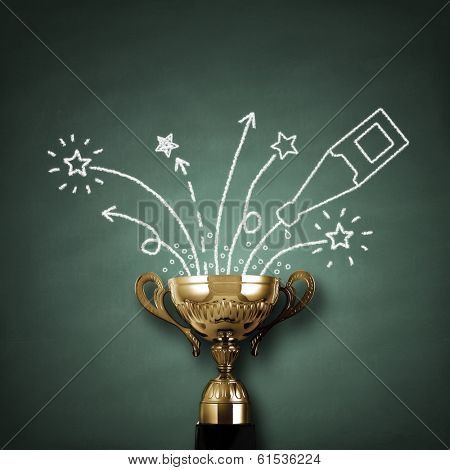 First place championship trophy or cup in front of blackboard with champagne and fireworks concept for winning and success