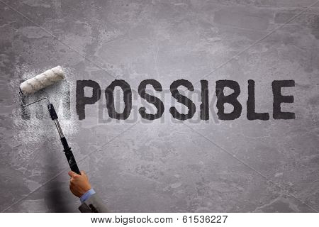 Changing the word impossible to possible by painting over and erasing part of the word with a paint roller on a concrete wall
