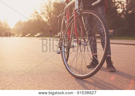 Young Woman Standing With Bicycle At Sunset