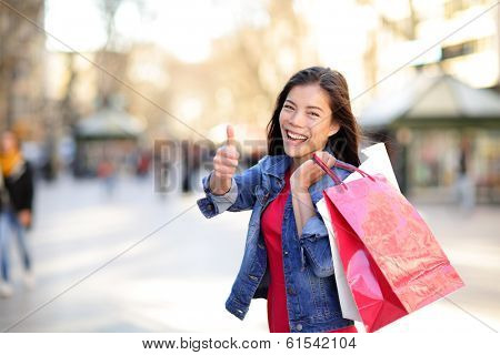 Shopping woman thumbs up on La Rambla, Barcelona, Spain. Happy Shopper girl holding shopping bags up excited outside on walking street. Mixed race Asian Caucasian female model.
