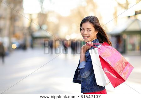 Woman shopping - shopper girl outdoors smiling happy holding shopping bags. Portrait of female shopper looking at camera on walking street La Rambla, Barcelona, Spain. Mixed race Asian woman.