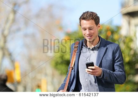 Young urban businessman professional on smartphone walking in street using app texting sms message on smartphone wearing jacket on Passeig de Gracia, Barcelona, Catalonia, Spain.