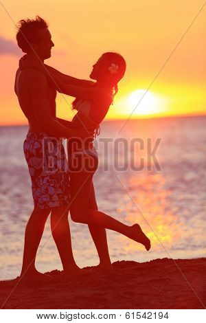 Romantic couple kissing on beach sunset on travel. Happy woman and man embracing in kiss on honeymoon romance in beautiful sun light. Multiracial couple, Image from Big Island, Hawaii.