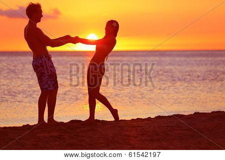 Romantic couple fun on beach sunset during travel. Happy woman and man holding hands playful on honeymoon romance in beautiful sun light. Multiracial couple, Image from Big Island, Hawaii.