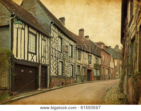 Gerberoy. Old street in medieval village. Gerberoy is a commune in the Oise department in northern France. Photo in retro style. Paper texture.