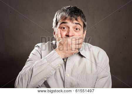 surprised man covering mouth with his hand
