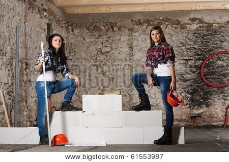 Two Young Long-haired Woman Built A New Wall From Blocks