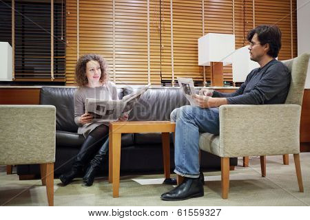 Pretty woman and man sit at table in hall with newspapers and look at each other