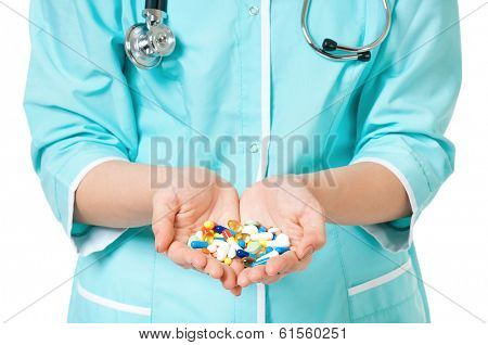 Cropped image of female doctor holding pills on white