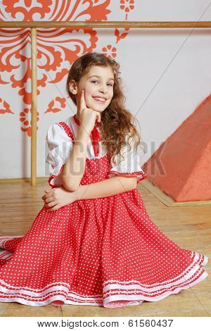Smiling curly girl in red folk costume poses on wooden floor