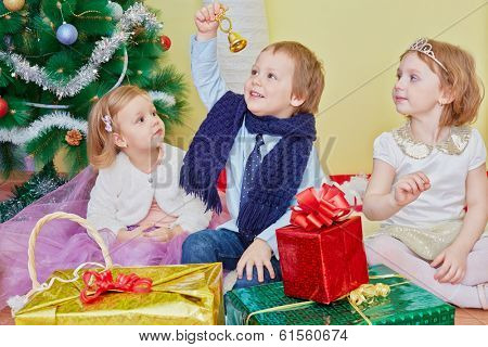 Three children sit on furry rug under christmas tree, boy rings hand bell which he holds in his hand extended upwards