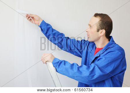 Worker in blue clothes works with painting fiberglass in new apartment
