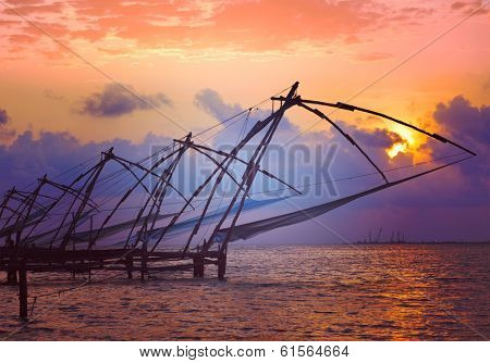 Vintage retro hipster style travel image of Kochi chinese fishnets on sunset with grunge texture overlaid. Fort Kochin, Kochi, Kerala, India