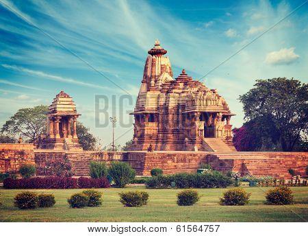Vintage retro hipster style travel image of Khajuraho Devi Jagdamba temple and mahadev mandapa on sunrise. Khajuraho, India