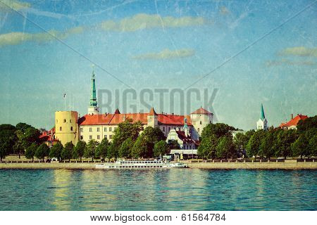Vintage retro hipster style travel image of  View of Riga Castle over Daugava river with grunge texture overlaid. Riga, Latvia