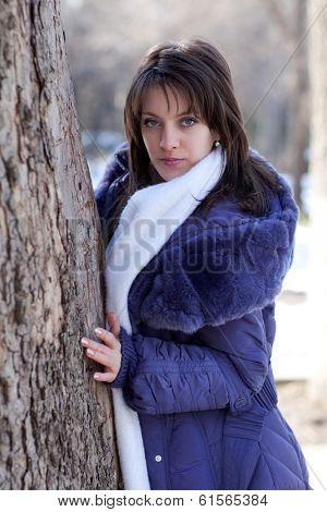 Beautiful girl peeps through the trees