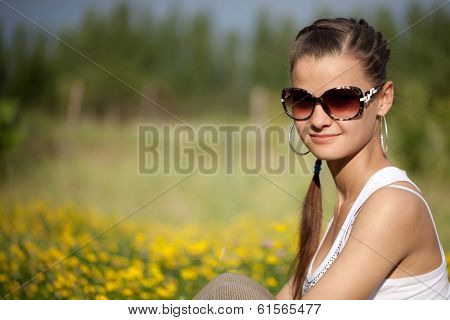 Portrait of a beautiful girl in sunglasses on a yellow-green meadow