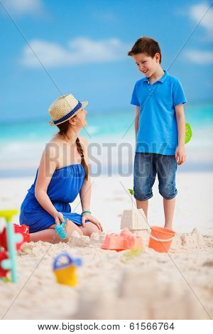 Mother and son building sandcastle at beach