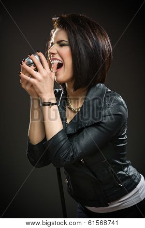 Half-length portrait of female rock musician wearing black jacket and handing mic on grey background. Concept of music and rave