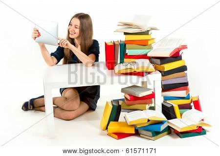 Girl Reading Something On Tablet With Heaps Of Unnecessary Books