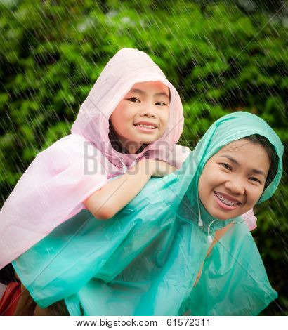 Asian Little Girl Enjoying The Rain Dressed In A Raincoat