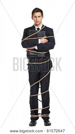 Full-length portrait of businessman handing briefcase who tied with the rope, isolated on white. Concept of slavery and violence