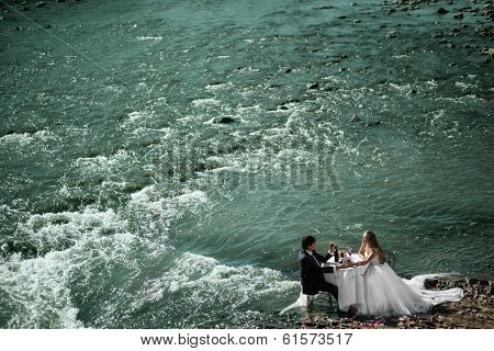 Wedding Couple Sitting At The Table And Celebrating Their Marriage On The River, General Up View