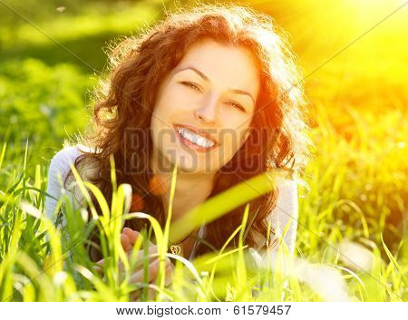 Beautiful Spring Young Woman Outdoors Enjoying Nature. Healthy Smiling Girl in Green Grass. Spring Meadow. Beautiful Lady Lying on the field. Backlit