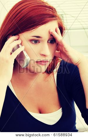 Upset, sad and worried by problems young woman sitting and talking by the phone.