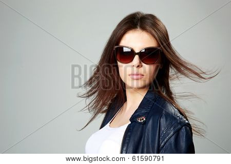 Studio shot of a young model in leather jacket and sunglasses on gray background