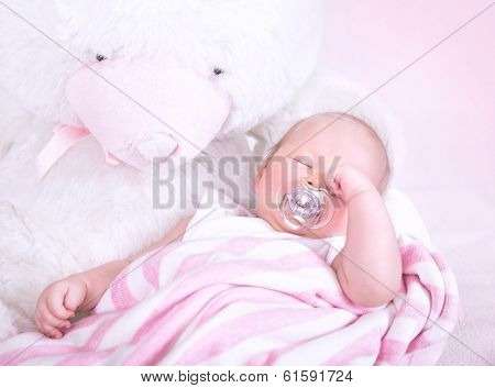 Cute newborn baby sleeping with pacifier in mouth, lying down on big white soft toy teddy bear, peaceful nap, happy childhood concept