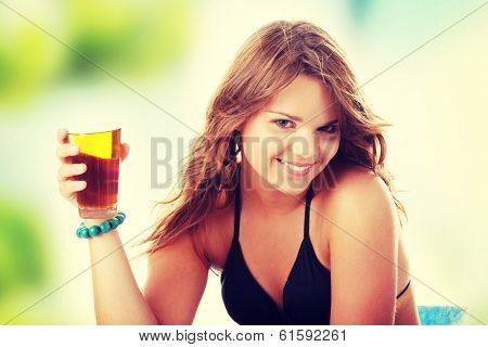 Young woman in bikini drinking ice tea