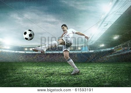 Soccer player with ball in action in rain.