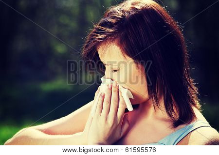 Young woman with allergy during sunny day is wiping her nose. Girl in summer dress with runny nose, having allergy and holding a tissue next to her face.