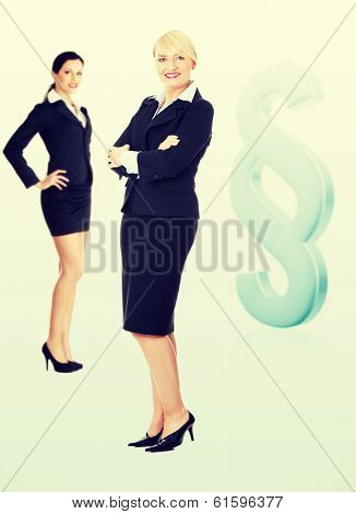 Two female lawyers standing next to big paragraph sign