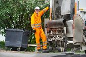 stock photo of garbage bin  - Worker of recycling garbage collector truck loading waste and trash bin - JPG