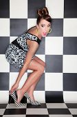 pic of bow-legged  - Attractive surprised young woman wearing high heels on checkered background - JPG
