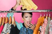 stock photo of annoyance  - Time for refreshing wardrobe young attractive surprised woman searching for clothing in a closet - JPG