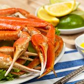 stock photo of cooked crab  - Snow Crab legs with fresh lemon slices and butter sauce - JPG