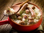 stock photo of creole  - risotto with sausage over red casserole - JPG