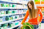 stock photo of grocery cart  - Young woman with shopping cart in supermarket looking for groceries - JPG