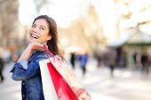 stock photo of girl walking away  - Shopping woman happy and looking away at copy space outdoors - JPG