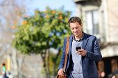 image of outdoor  - Young urban professional man using smart phone - JPG