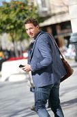 Young business man on smart phone walking in street with smartphone smiling wearing jacket on Passei