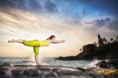 picture of virabhadrasana  - Woman doing yoga on the stone nearby ocean at lighthouse background in Kovalam Kerala India - JPG