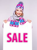 stock photo of outerwear  - Adult smiling woman in winter outerwear holds the white banner with sale word on it - JPG