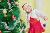 Smiling little girl dressed in furry mantle, knitted dress and santa cap decorates christmas tree poster