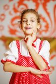 Beautiful girl in red folk costume poses and smiles near wall with pattern